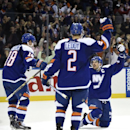 New York Islanders center John Tavares (91) celebrates his power play goal in overtime against the Washington Capitals with defenseman Nick Leddy (2) and center Ryan Strome (18) in an NHL hockey game at Nassau Coliseum on Wednesday, Nov. 26, 2014, in Unio