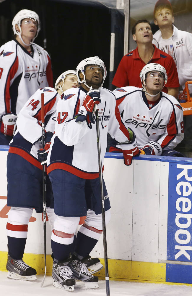 Washington Capitals players Mkhail Grabovski (84), Joel Ward (42) and Marcus Johansson (90) watch the overhead monitor to see if Ward scored a goal against the Florida Panthers during the second period of a NHL hockey game in Sunrise, Fla., Friday, Dec. 13, 2013