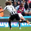 Aston Villa's Gabriel Agbonlahor, right, has a shot towards goal past Newcastle United's captain Fabricio Coloccini, left, during their English Premier League soccer match at St James' Park, Newcastle, England, Sunday, Feb. 23, 2014