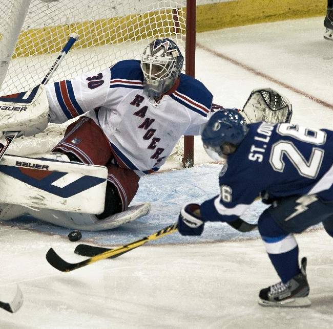 New York Rangers goalie Henrik Lundqvist (30) stops a shot from Tampa Bay Lightning's Martin St. Louis (26) during the third period of an NHL hockey game, Sunday, Dec. 29, 2013, in Tampa, Fla. Lundqvist had 37 saves in a 4-3 win over the Lightning