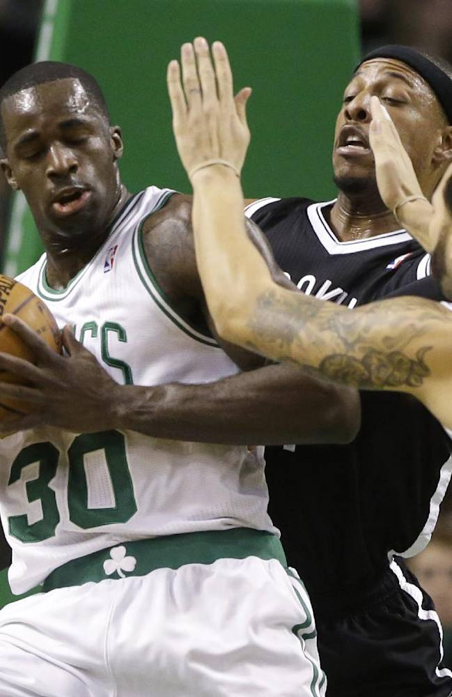 Boston Celtics forward Brandon Bass (30), tries to drive past Brooklyn Nets forward Paul Pierce, center, and Deron Williams (8) in the first quarter of an NBA basketball game, Sunday, Jan. 26, 2014, in Boston