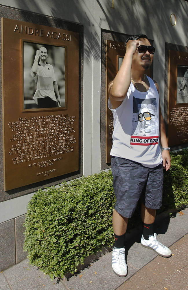 A tennis fan poses next to a plaque of Andre Agassi in the Court of Champions at the Billie Jean King Tennis Center during the second round of the 2014 U.S. Open tennis tournament, Wednesday, Aug. 27, 2014, in New York