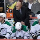 Dallas Stars coach Lindy Ruff, top, watches from the bench as Travis Morin, Tyler Seguin and Jamie Benn, from left, sit during the third period of an NHL hockey game against the Vancouver Canucks on Wednesday, Dec. 17, 2014, in Vancouver, British Columbia