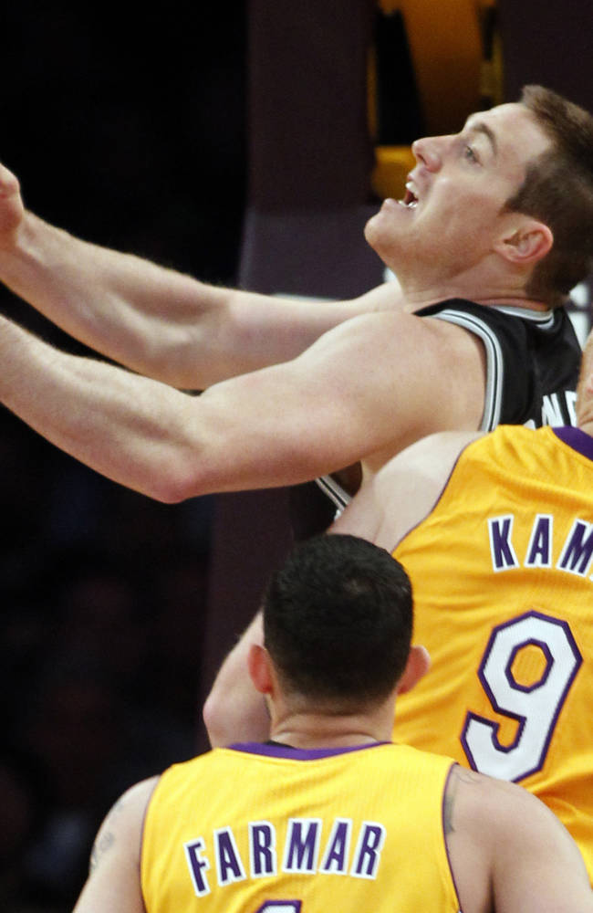 San Antonio Spurs forward Aron Baynes, center, of Australia, shoots with Los Angeles Lakers center Chris Kaman (9) and Lakers guard Jordan Farmar, below, defending in the first quarter during an NBA basketball game Friday, Nov. 1, 2013, in Los Angeles