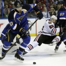 Chicago Blackhawks' Andrew Shaw (65) collides with St. Louis Blues' David Perron (57) as Alex Pietrangelo (27) clears the puc