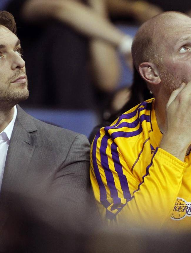 Los Angeles Lakers forward Pau Gasol, left, of Spain, sits on the bench with Lakers center Chris Kaman, checking out the scoreboard in an NBA basketball preseason game against the Golden State Warriors on Saturday, Oct. 5, 2013, in Ontario, Calif