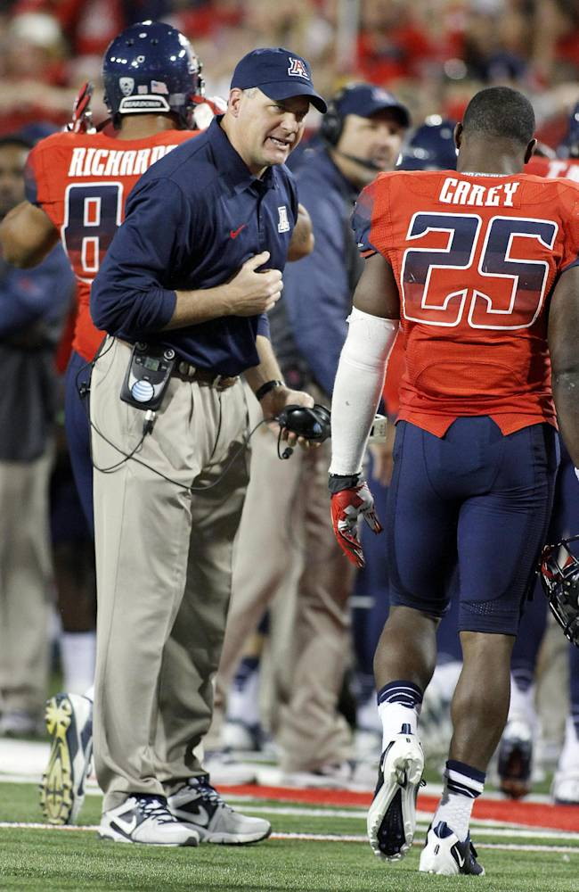 Arizona's head coach Rich Rodriguez, left, is happy with his running back Ka'Deem Carey (25) in the second half against UCLA in an NCAA college football game on Saturday, Nov. 9, 2013 in Tucson, Ariz