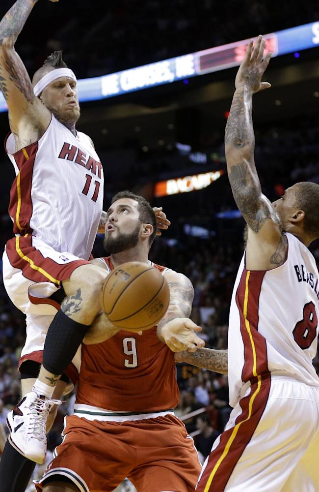 Milwaukee Bucks' Miroslav Raduljica (9), of Serbia, attempts to shoot as Miami Heat's Chris Andersen (11) and Michael Beasley (8) defend during the second half of an NBA basketball game Tuesday, Nov. 12, 2013, in Miami. The Heat won 118-95