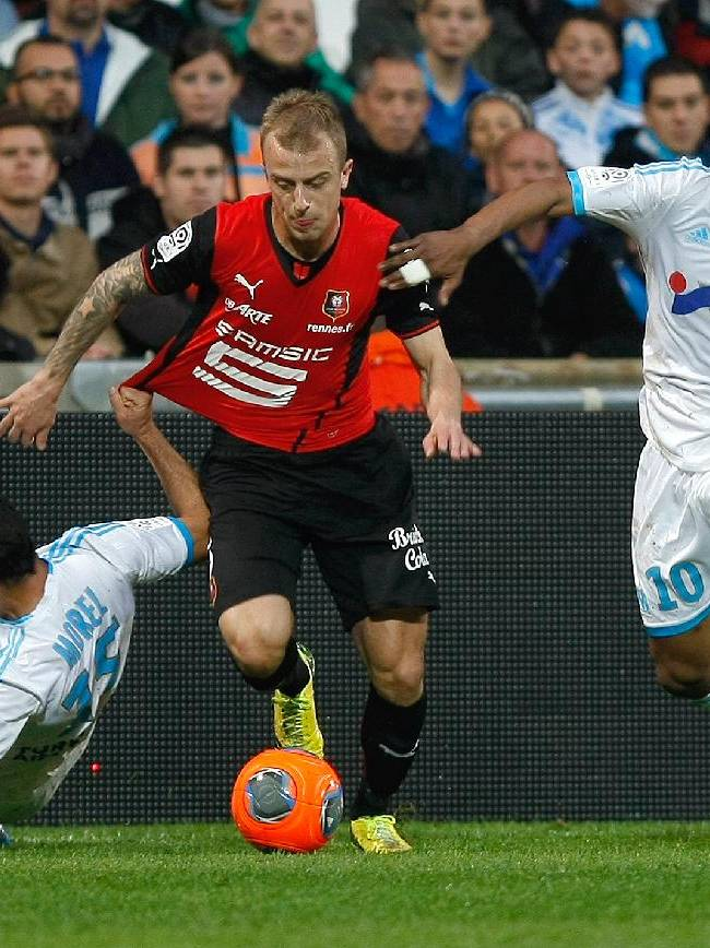 Rennes' Polish forward Kamil Grosicki, center,  challenges for the ball with Marseille's Ghanaian forward Andre Ayew, right, and Marseille's French defender Jeremy Morel, during their League One soccer match, at the Velodrome Stadium, in Marseille, southern France, Saturday, March 22, 2014
