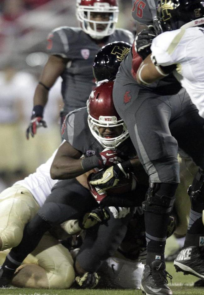 Washington State running back Marcus Mason, center, protects the ball as he is tackled by Idaho defenders during the second half of an NCAA college football game Saturday, Sept. 21, 2013, in Pullman, Wash. Washington State won 42-0 in the first meeting between the teams that are only eight miles apart since 2007