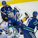 Vancouver Canucks' Dan Hamhuis (2) checks Nashville Predators' Mike Ribeiro (63) collide with goalie Eddie Lack, of Sweden, during the second period of an NHL hockey game in Vancouver, British Columbia on Sunday, Nov. 2, 2014 The Associated Press