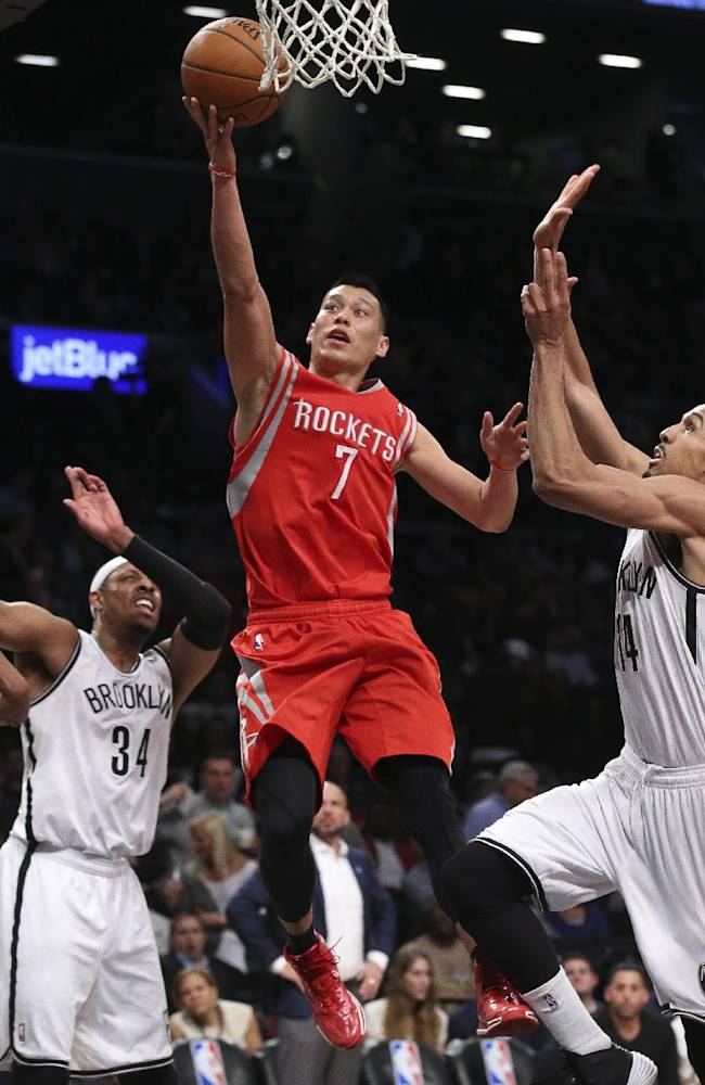 Houston Rockets guard Jeremy Lin (7) shoots against Brooklyn Nets guard Shaun Livingston (14) as forward Paul Pierce (34) looks on during the second half of their NBA basketball game at the Barclays Center, Tuesday, April 1, 2014, in New York