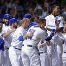 Chicago Cubs players including Anthony Rizzo, center, and Starlin Castro, right of center, celebrate after Kris Bryant hit a game winning two run home run against the Colorado Rockies during the ninth inning of a baseball game in Chicago, Monday, July 27, 2015. The Cubs won 9-8. (AP Photo/Andrew A. Nelles)