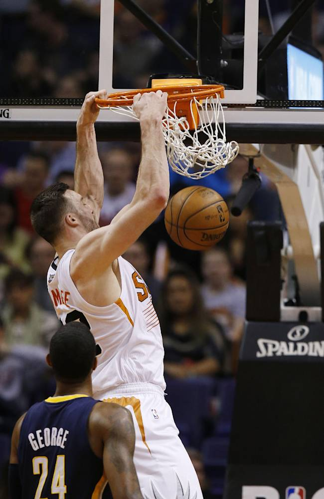 Phoenix Suns' Miles Plumlee, right, dunks as Indiana Pacers' Paul George (24) looks on during the first half of an NBA basketball game, Wednesday, Jan. 22, 2014, in Phoenix