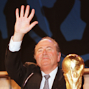 FILE - In this Monday June 8, 1998 file photo, Switzerland's Sepp Blatter next to a replica of the World Cup trophy, waves after being elected FIFA president, the world's soccer governing body, in Paris. FIFA has been routinely called