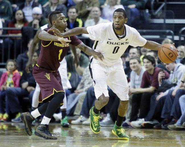 Oregon forward Mike Moser, right, dribbles against Arizona State guard Jahii Carson during the second half of an NCAA college basketball game in Eugene, Ore., Tuesday, March 4, 2014.  Moser led Oregon with 22 points and 17 rebounds as they beat Arizona State 85-78