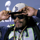 Seattle Seahawks' Marshawn Lynch adjusts his cap during an interview for NFL Super Bowl XLIX football game, Thursday, Jan. 29, 2015, in Phoenix. The Seahawks play the New England Patriots in Super Bowl XLIX on Sunday, Feb. 1, 2015. (AP Photo/Matt York)