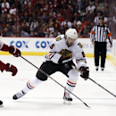 Chicago Blackhawks defenseman Nick Leddy (8) carries the puck in front of Phoenix Coyotes defenseman Connor Murphy in the first period of an NHL hockey game on Saturday, Nov. 30, 2013, in Glendale, Ariz The Associated Press