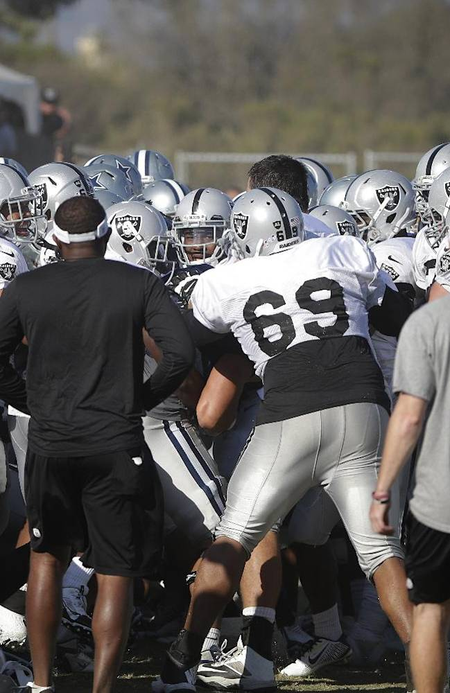The Oakland Raiders and the Dallas Cowboys players engage in a scuffle during a joint football practice on Tuesday, Aug. 12, 2014, in Oxnard, Calif