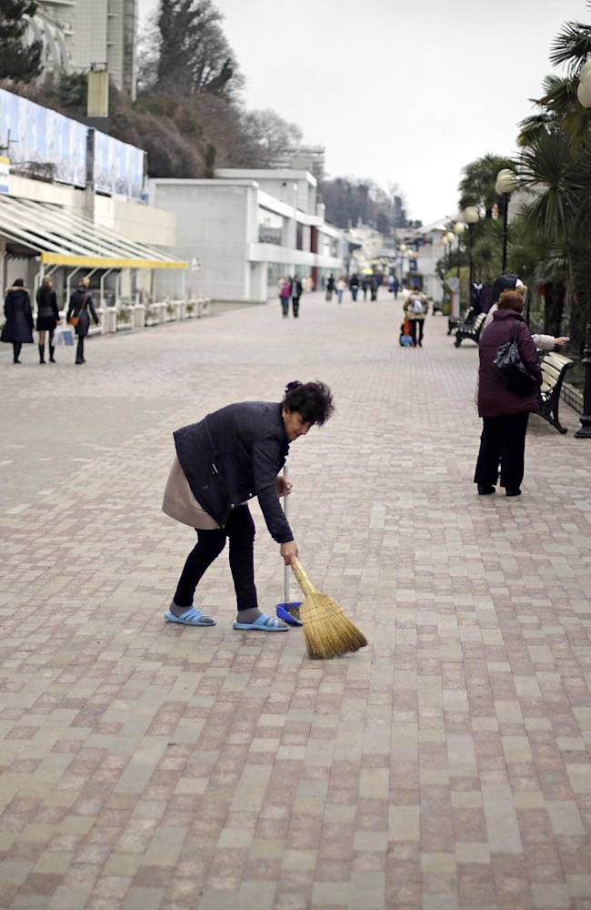 A woman sweeps the boardwalk in front of souvenir shops along the Black Sea, Wednesday, Jan. 29, 2014, in Sochi, Russia, home of the upcoming 2014 Winter Olympics