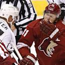 Arizona Coyotes' Martin Hanzal (11) grimaces after being hit with a stick in the face as Los Angeles Kings' Jeff Carter, left, skates past during the second period of a preseason NHL hockey game Monday, Sept. 22, 2014, in Glendale, Ariz. (AP Photo/Ross D. Franklin)