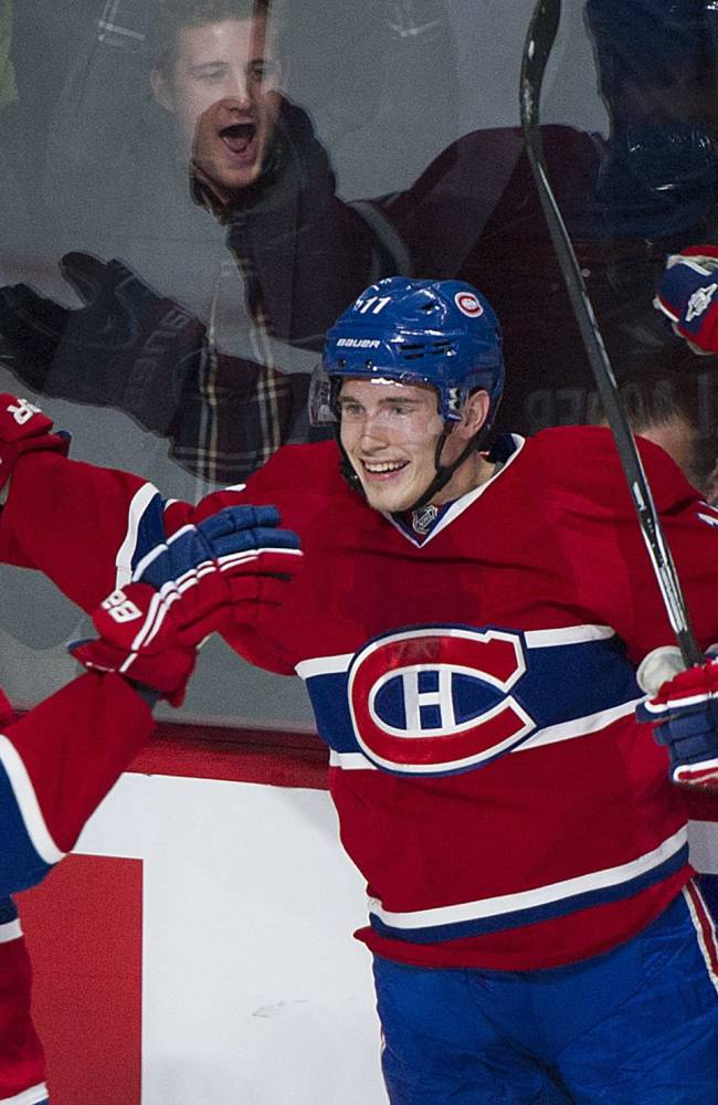 Montreal Canadiens' Brendan Gallagher, center, celebrates with teammates P.K. Subban, right, and Mike Blunden after scoring against the Edmonton Oilers during the first period of an NHL hockey game in Montreal, Tuesday, Oct. 22, 2013