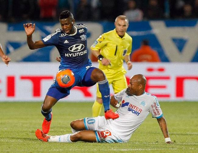 Lyon's Cameroonian defender Henri Bedimo, left, controls the ball past Marseille's Ghanaian forward Andre Ayew during their League One soccer match at the Velodrome Stadium in Marseille, southern France, Sunday May 4, 2014
