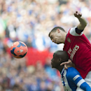 Arsenal's Thomas Vermaelen, top head the ball with Wigan Athletic's Marc-Antoine Fortune during their English FA Cup semifinal soccer match, at the Wembley Stadium in London, Saturday, April 12, 2014