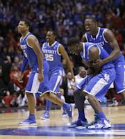 Kentucky's Alex Poythress and Aaron Harrison, right, celebrate after an NCAA Midwest Regional semifinal college basketball tournament game against the Louisville Saturday, March 29, 2014, in Indianapolis. Kentucky won 74-69. (AP Photo/David J. Phillip)