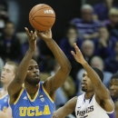 UCLA's Shabazz Muhammad (15) passes around the defense of Washington's Scott Suggs (15) during the first half of an NCAA college basketball game, Saturday, March 9, 2013, in Seattle. (AP Photo/Ted S. Warren)