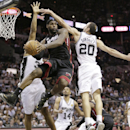 In this June 13, 2013 file photo, Miami Heat's LeBron James (6) passes between San Antonio Spurs' Boris Diaw (33), of France, and Manu Ginobili (20), of Argentina, during the second half at Game 4 of the NBA Finals, in San Antonio. A rematch of last yea