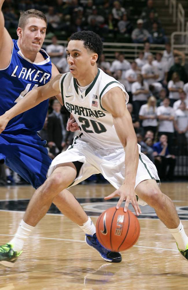Michigan State's Travis Trice (20) drives against Grand Valley State's Ernijs Ansons during the second half of an NCAA college basketball exhibition game, Tuesday, Oct. 29, 2013, in East Lansing, Mich. Michigan State won 101-52