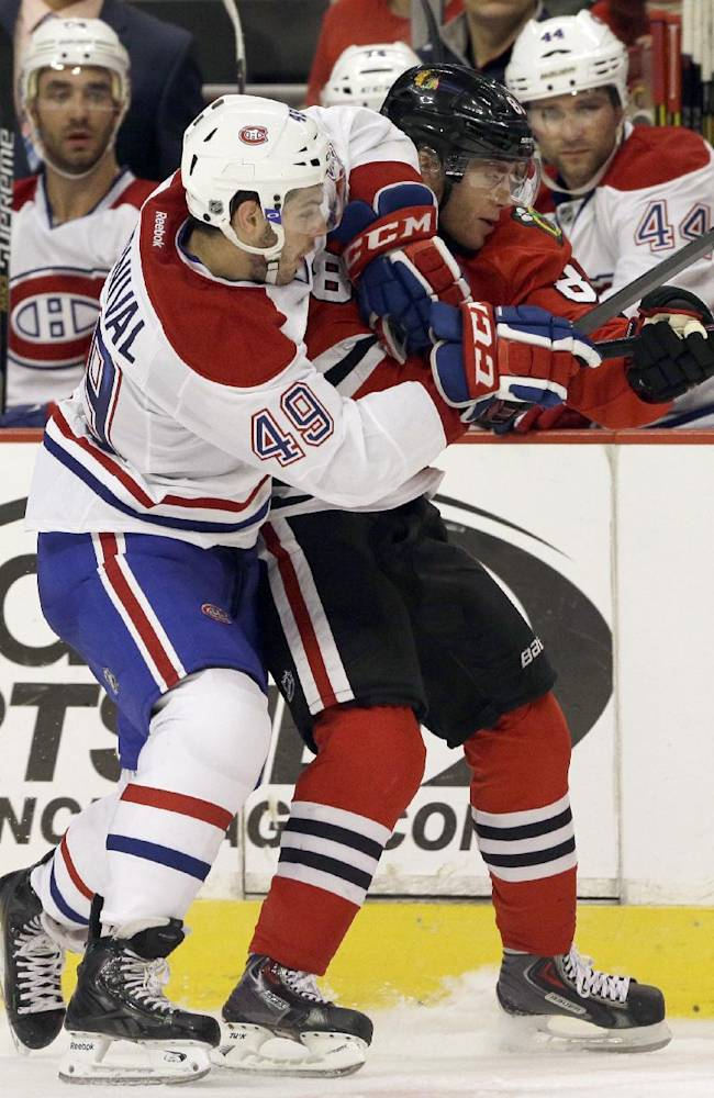 Montreal Canadiens left wing Michael Bournival (49) battles for the puck against Chicago Blackhawks right wing Patrick Kane (88) during the second period of a preseason NHL hockey game in Chicago, Wednesday, Oct. 1, 2014