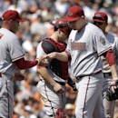 Arizona Diamondbacks pitcher Trevor Cahill, right, walks off the mound after being relieved by manager Kirk Gibson (23) during the fourth inning of a baseball game against the San Francisco Giants in San Francisco, Tuesday, April 8, 2014. The Giants won 7