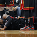 Miami Heat guard Dwyane Wade reacts after landing hard on his right knee during the first quarter of an NBA basketball game against the Minnesota Timberwolves in Minneapolis, Saturday, Dec. 7, 2013.Wade stayed in the game and scored 19 points as the Heat won 103-82. (AP Photo/Ann Heisenfelt)