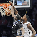 Brooklyn Nets' Andray Blatche, right, dunks the ball as he gets by Minnesota Timberwolves' Gorgui Dieng during the third quarter of an NBA basketball game Sunday, March 30, 2014, at Barclay's Center in New York. The Nets won 114-99 The Associated Press