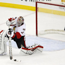 Ottawa Senators goalie Craig Anderson shoots on an empty New Jersey Devils net during the third period of an NHL hockey game, Wednesday, Dec. 17, 2014, in Newark, N.J. The Senators won 2-0 The Associated Press