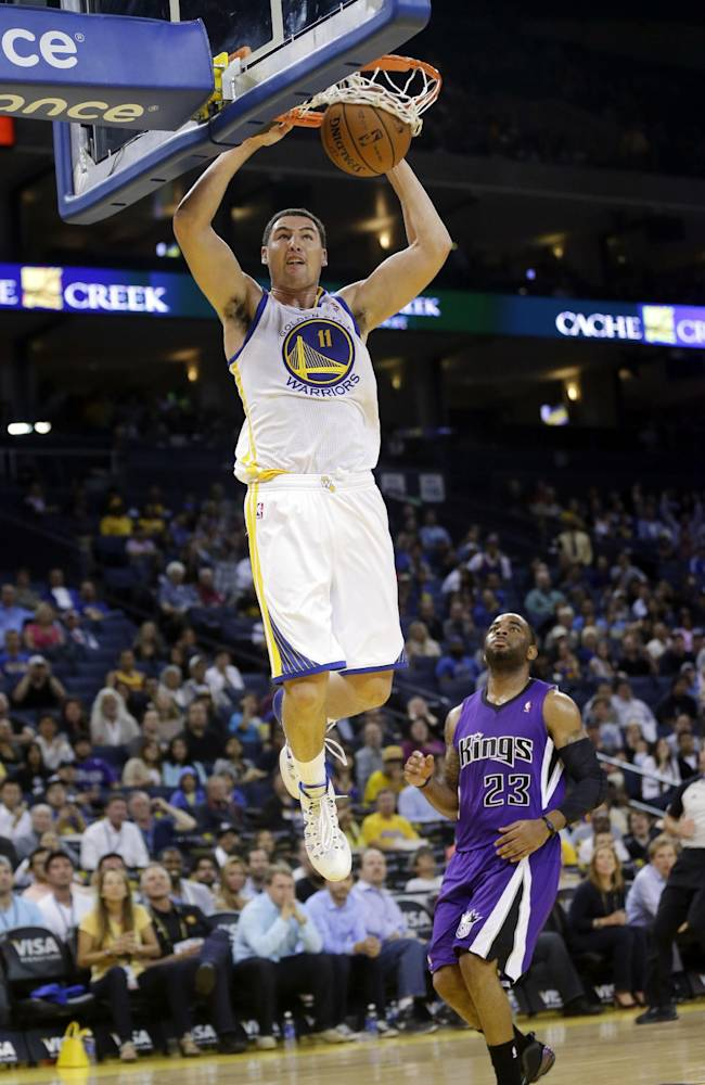 Golden State Warriors' Klay Thompson dunks past Sacramento Kings' Marcus Thornton (23) during the second half of an NBA preseason basketball game Monday, Oct. 7, 2013, in Oakland, Calif