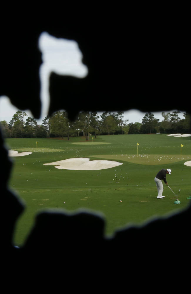 AP10thingsToSee - Seen through a cutout of the Masters golf tournament logo, Lucas Glover hits on the practice range during a practice round in Augusta, Ga. on Tuesday, April 8, 2014