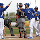 Kansas City Royals' Billy Butler (16) congratulates Eric Hosmer, center, following Hosmer's three-run home run off of Cincinnati Reds' Johnny Cueto that scored Jarrod Dyson, right rear, and Justin Maxwell in the in the third inning of a spring training ba