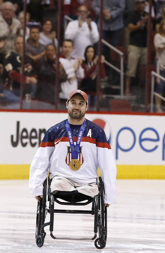 Josh Sweeney, U.S. sled hockey team member for the Paralympic Games, gets a standing ovation from the crowd as he is introduced before an NHL hockey game between the Phoenix Coyotes and the Minnesota Wild, Saturday, March 29, 2014, in Glendale, Ariz. Sweeney a former Marine sergeant, scored a breakaway goal as the United State defeated Russia 1-0 to win the gold medal earlier this month