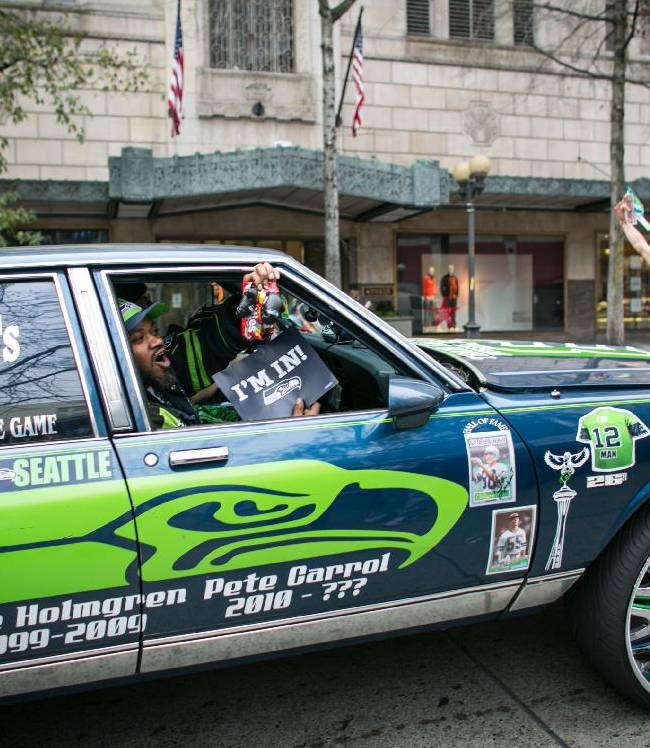 Seattle Seahawks fans drive a Seawks-themed car past Westlake Park during a rally for the NFL football team Friday, Jan. 17, 2014, in Seattle. The Seahawsk play the San Francisco 49ers on Sunday for the NFC championship