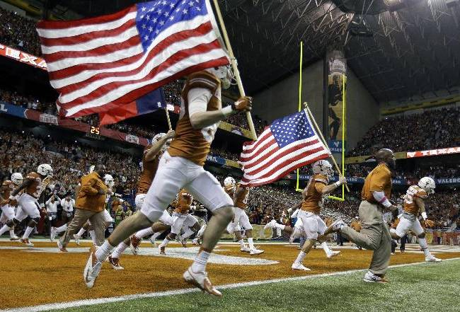 Texas players run onto the field for the Valero Alamo Bowl NCAA college football game against Oregon, Monday, Dec. 30, 2013, in San Antonio