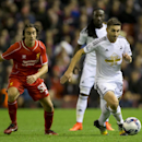 Swansea's Angel Rangel, right, keeps the ball from Liverpool's Lazar Markovic during the English League Cup soccer match between Liverpool and Swansea at Anfield Stadium, Liverpool, England, Tuesday, Oct. 28, 2014