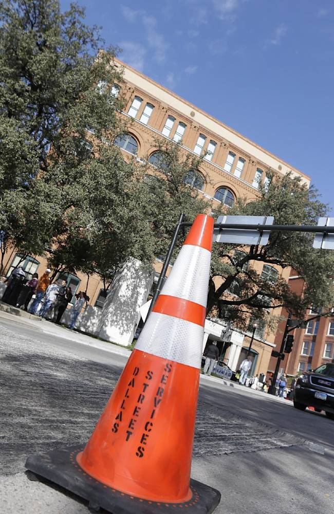 A work cone marks off a section of street surface that was ripped up near the Sixth Floor Museum, in the background, on Dealey Plaza where JFK was assassinated in downtown Dallas,  Tuesday, Nov. 19, 2013. Days before Dallas' observance of JFK assassination date, 'X's marking shooting spots on the street were removed by city work crews as the city prepares for Friday's events that will solemnly commemorate the 50th anniversary of JFK being assassinated