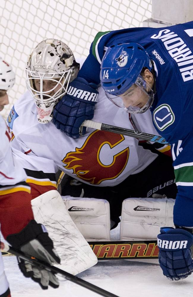 Vancouver Canucks left wing Alex Burrows (14) falls on Calgary Flames goalie Karri Ramo (31) as Calgary Flames defenseman Mark Giordano (5) tries to clear the puck from in front of the net during the second period of NHL action in Vancouver, British Columbia Saturday Jan. 18, 2014