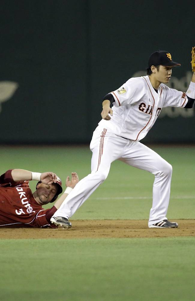 Yomiuri Giants shortstop Hayato Sakamoto, center, appeals to the second-base umpire after tagging out Rakuten Eagles' Casey McGehee, below, at second, in the seventh inning of Game 3 of baseball's Japan Series at the Tokyo Dome in Tokyo, Tuesday, Oct. 29, 2013