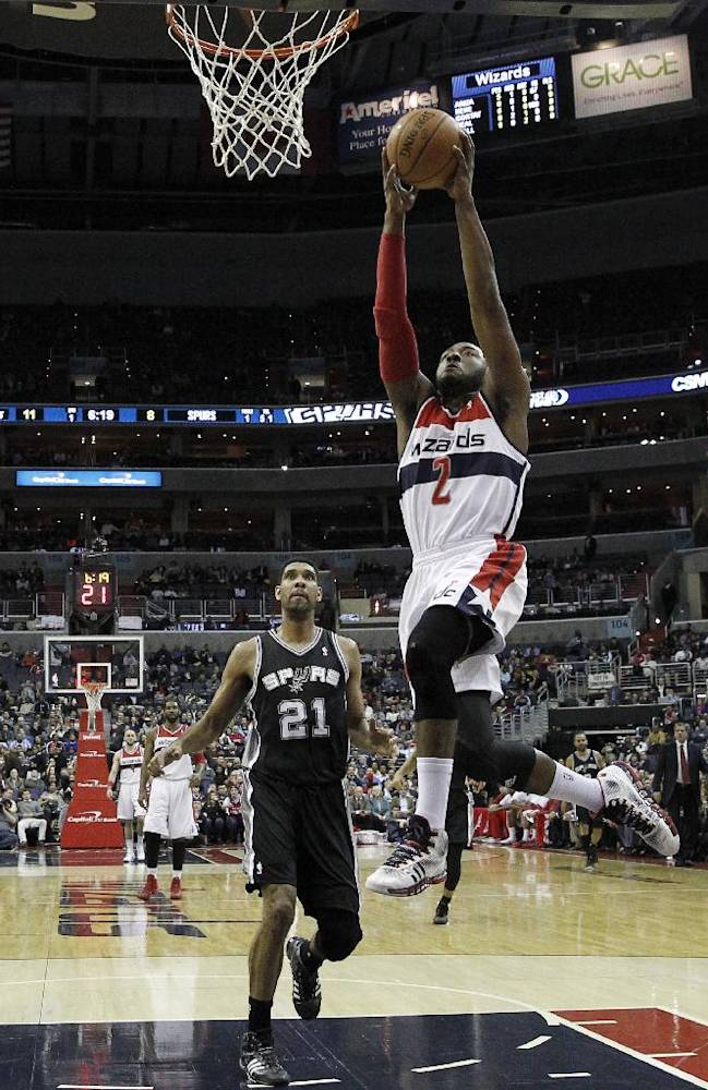 Washington Wizards guard John Wall (2) dunks the ball in front of San Antonio Spurs forward Tim Duncan (21) in the first half of an NBA basketball game on Wednesday, Feb. 5, 2014, in Washington