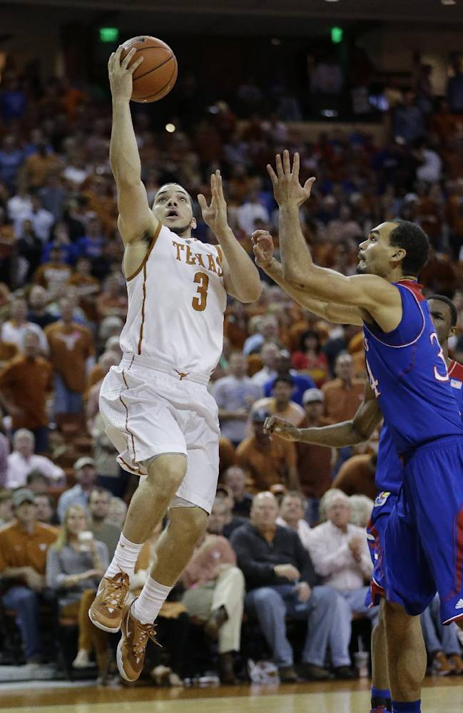 File- In this Saturday, Feb. 1, 2014 photo, Texas' Javan Felix (3) shoots over Kansas' Perry Ellis (34) during the first half of an NCAA college basketball game in Austin, Texas. Felix will miss the Longhorns' game at TCU on Tuesday night because of a concussion, the school announced Sunday