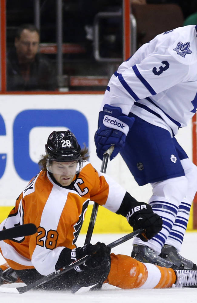 Philadelphia Flyers' Claude Giroux, left, tries to pass the puck after a collision with Toronto Maple Leafs' Dion Phaneuf during the first period of an NHL hockey game, Friday, March 28, 2014, in Philadelphia